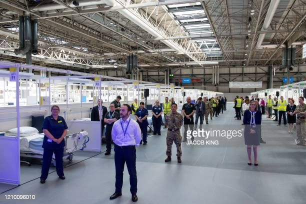 Attendees including members of the military health professionals and contactors who helped during the construction observe social distancing measures...