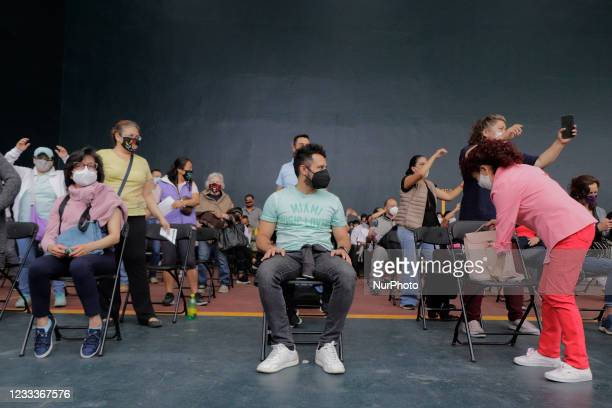 Attendees inside a vaccination unit at Campo Marte, Mexico City, dance after being inoculated with a dose of the Pfizer-BioNTech COVID-19 vaccine...