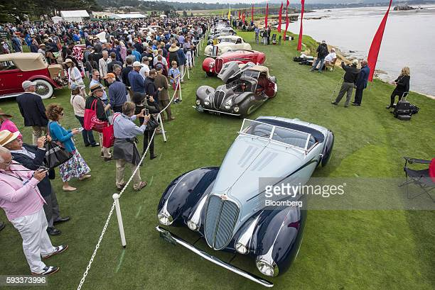 Attendees inspect a 1937 Delahaye 135 M Figoni et Falaschi Cabriolet motor vehicle during the 2016 Pebble Beach Concours d'Elegance in Pebble Beach...