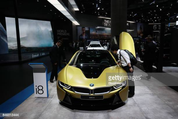 Attendees inspect a BMW i8 electric automobile manufactured by Bayerische Motoren Werke AG on the first media preview day of the IAA Frankfurt Motor...