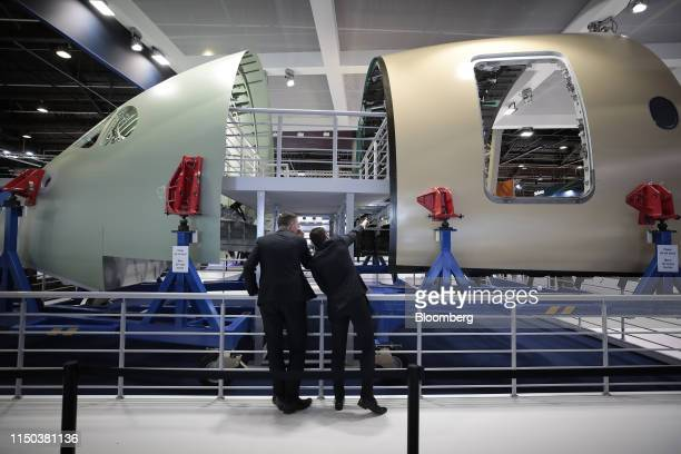 Attendees inspect a fuselage and nose cone display at the Stelia Aerospace exhibition stand during the 53rd International Paris Air Show at Le...