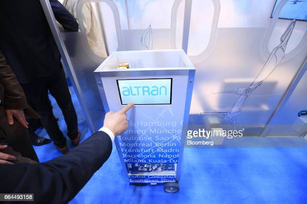 Attendees inspect a robotic waiter catering device manufactured by Altran Technologies SA at the Aircraft Interiors Expo in Hamburg, Germany, on...