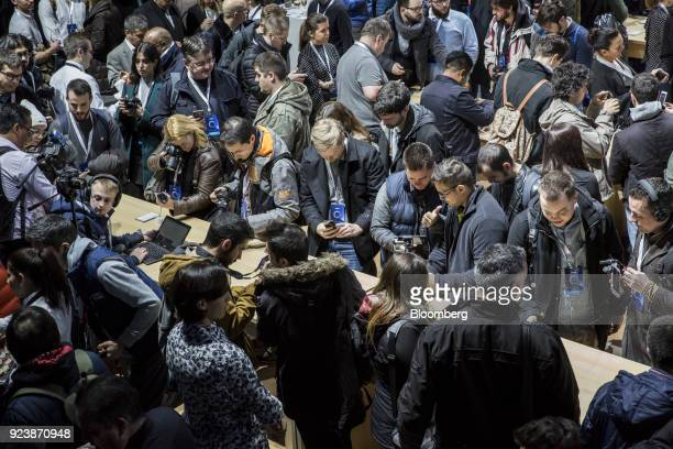 Attendees inspect Alcatel smartphone devices on display during an AlcatelLucent SA launch event ahead of the Mobile World Congress in Barcelona Spain...