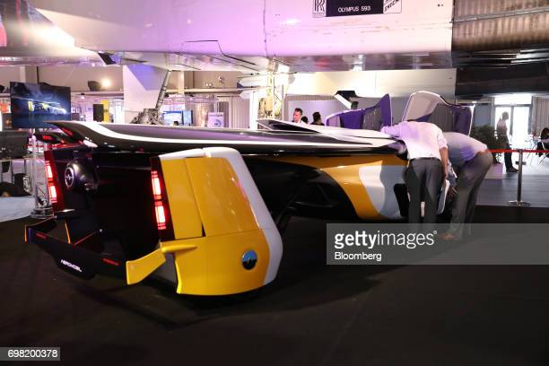 Attendees inspect an AeroMobil flying car as it stands on display during the 53rd International Paris Air Show at Le Bourget in Paris France on...