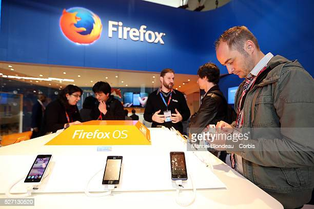 Attendees inspect mobile devices which run on a Firefox operating system at the Mozilla Corp pavilion during the Mobile World Congress at the Fira...