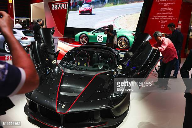 Attendees inspect the LaFerrari Aperta automobile, produced by Ferrari NV, during the second press day of the Paris Motor Show at Porte de Versailles...
