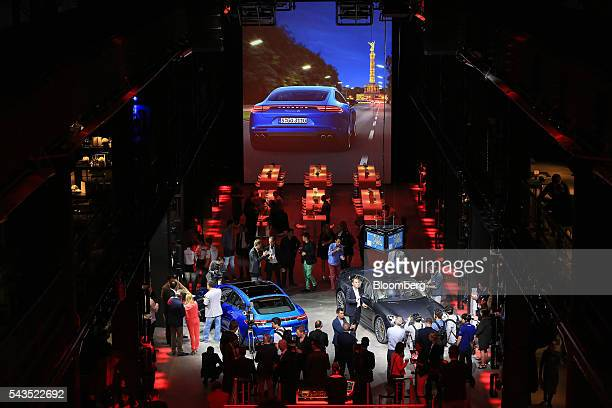 Attendees inspect the new Porsche AG Panamera 4S coupe, left, and Porsche Panamera Turbo coupe as Volkswagen AG's luxury unit unveil the automobile's...