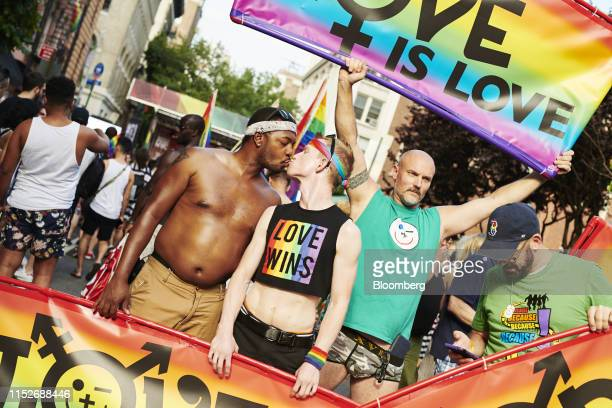 Attendees kiss as they hold signs during a Stonewall Inn 50th anniversary commemoration rally in New York US on Friday June 28 2019 Fifty years ago...