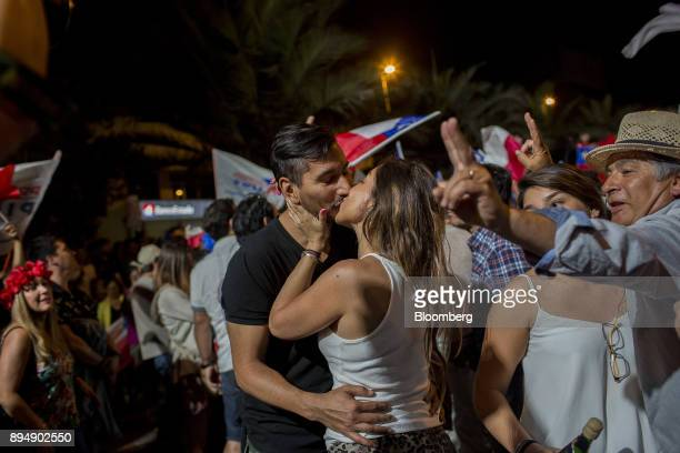 Attendees kisses to celebrate exit poll results at the National Renewal party headquarters after the second round presidential general elections in...