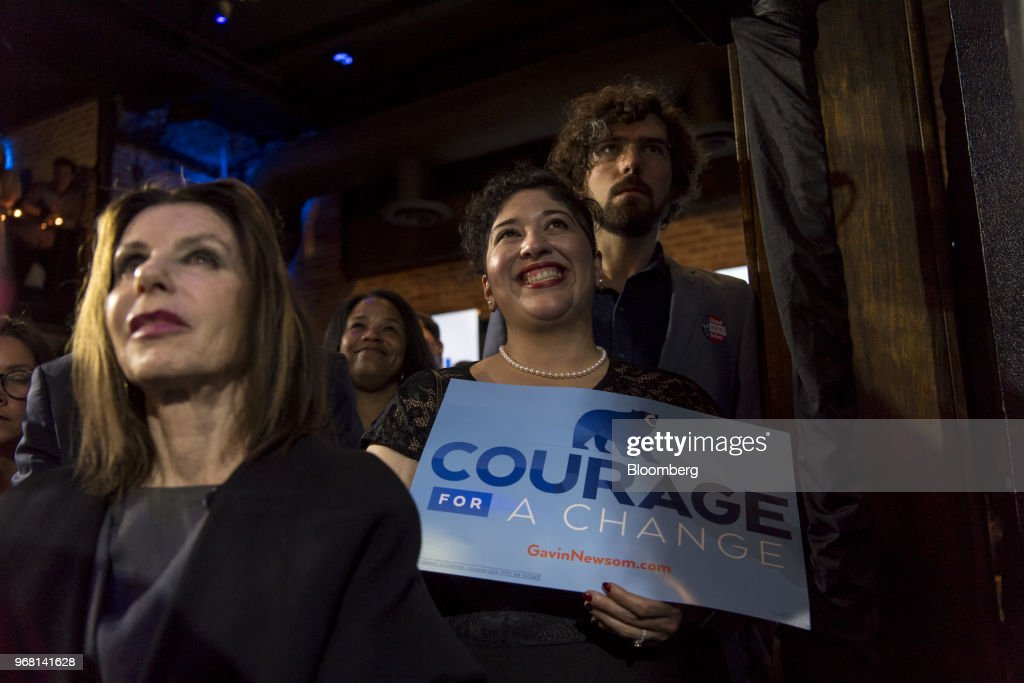Attendees listen as Gavin Newsom, Democratic candidate for governor of California, not pictured, speaks during a primary election watch party in San Francisco, California, U.S., on Tuesday, June 5, 2018. Lieutenant GovernorNewsomand Republican businessman John Cox won the most votes in Californias gubernatorial primary, advancing to a general election that will test the states position as leader of the resistance to PresidentDonald Trump. Photographer: David Paul Morris/Bloomberg via Getty Images