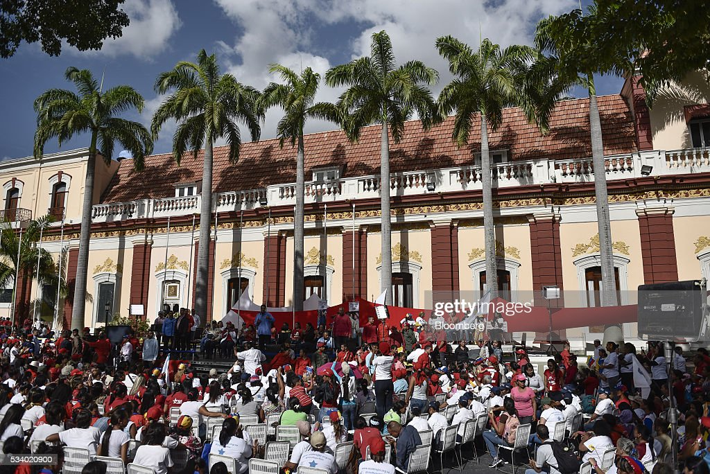 Attendees listen as Nicolas Maduro, Venezuela's president, center, speaks during a rally for women and peace at the Miraflores Palace in Caracas, Venezuela on Tuesday, May 24, 2016. On Tuesday, hundreds of women took to the streets in a show of support for President Maduro and against what they called the violent demonstrations by the opposition. Photographer: Carlos Becerra/Bloomberg via Getty Images