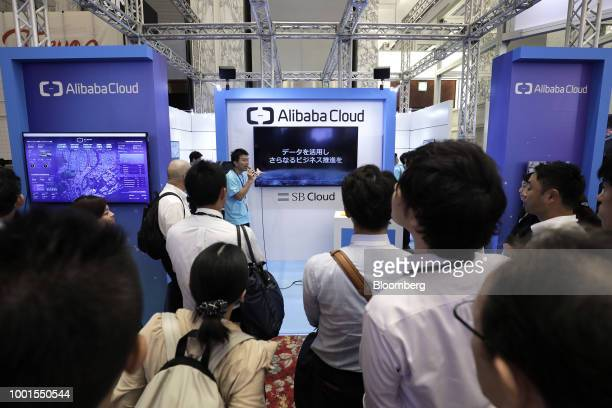 Attendees listen to an attendant explaining about cloud computing services by Alibaba Cloud a subsidiary of Alibaba Group Holding Ltd at the SoftBank...