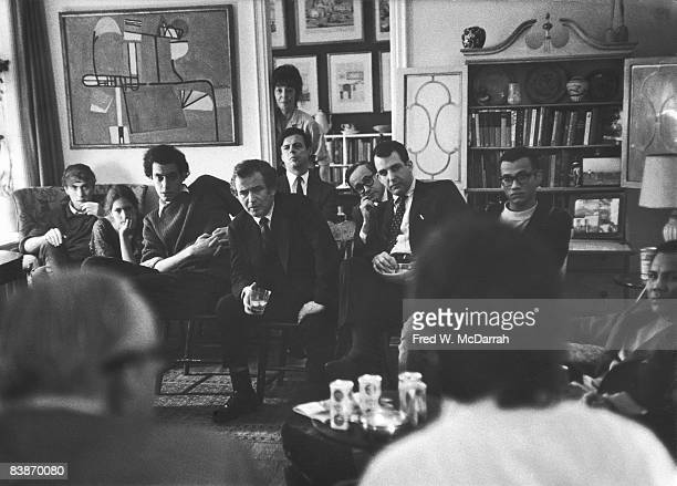 Attendees listen to speakers at an informal meeting of Students for a Democratic Society leadership and sympathetic audience members in the apartment...