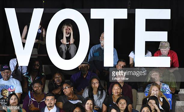 Attendees listen to US President Barack Obama speak during a campaign rally for Democratic presidential nominee Hillary Clinton at Cheyenne High...