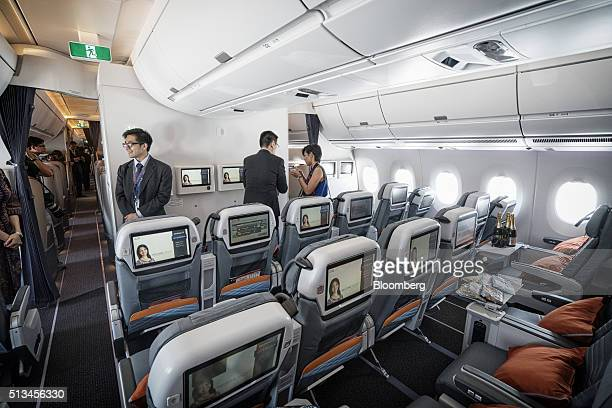 Attendees look around the premium economy class cabin of an Airbus SE A350 aircraft operated by Singapore Airlines Ltd during an arrival ceremony at...