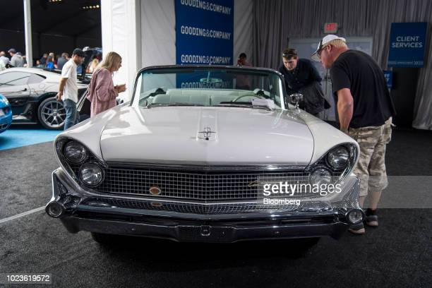 Attendees look at a 1959 Lincoln Continental Mark IV Convertible vehicle on display during the Gooding and Company auction at the 2018 Pebble Beach...