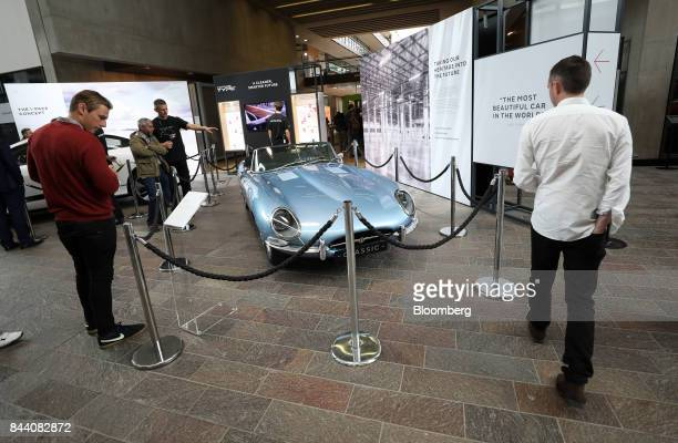 Attendees look at a battery versionof Jaguar's iconic EType roadster automobile standing on display at the annual tech fair of Tata Motors Ltd's...