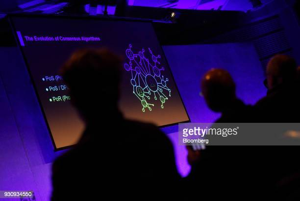 Attendees look at a diagram titled 'The Evolution of Consensus Algorithms' relating to blockchain developments on a screen during the Crypto Investor...