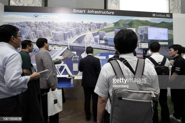 Attendees look at a display featuring SoftBank Group Corp's smart infrastructure solution and 5G wireless network technology at the SoftBank World...