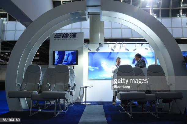 Attendees look at a display of Molon Labe Designs side-slip passenger seats at the Aircraft Interiors Expo in Hamburg, Germany, on Tuesday, April 4,...