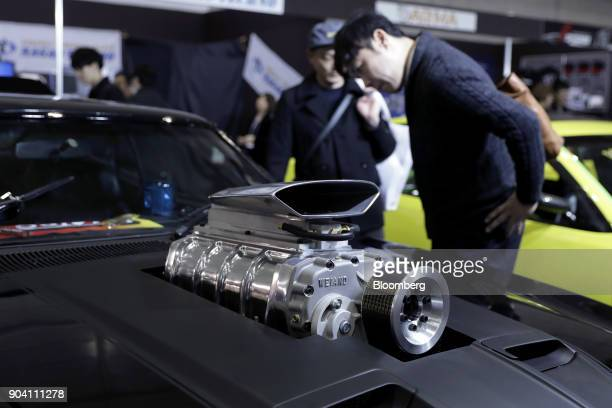 Attendees look at a Ford Motor Co thirdgeneration Falcon vehicle a reproduction of the car that appeared in the Mad Max films displayed at the Tokyo...