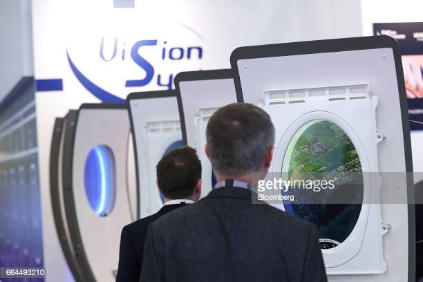 Attendees look at a new generation of electronically dimmable airline windows manufactured by Vision Systems at the Aircraft Interiors Expo in...