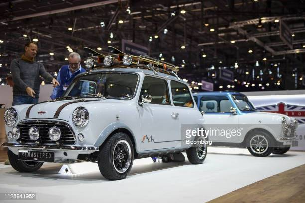 Attendees look at a remastered Mini on the David Brown stand ahead of the 89th Geneva International Motor Show in Geneva Switzerland on Monday March...