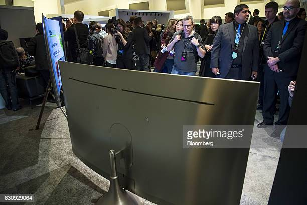 Attendees look at a Samsung Electronics Co Q8C QLED TV part of the Q8 series sits on display during a Samsung press event at the 2017 Consumer...