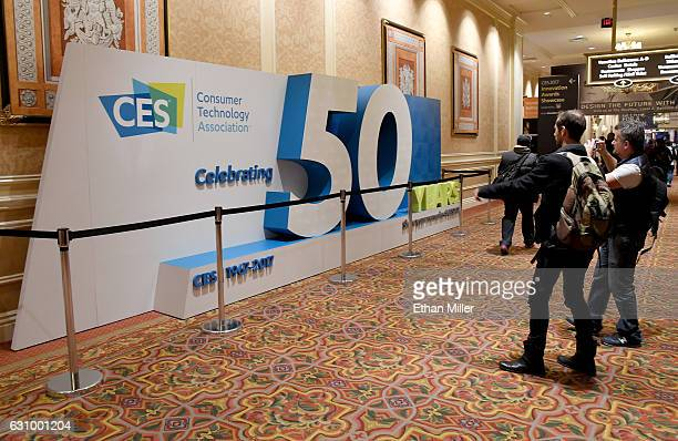 Attendees look at a sign marking the 50th anniversary of CES at The Venetian Las Vegas on January 4 2017 in Las Vegas Nevada CES the world's largest...