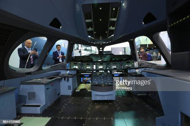 Attendees look at an aircraft cockpit section with an interior manufactured by Hutchinson Composite Industrie at the 2017 Aircraft Interiors Expo in...