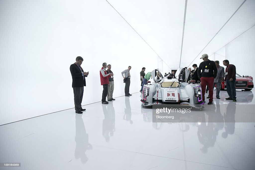Attendees look at an Audi AG R18 e-tron Quattro vehicle during the 2013 Consumer Electronics Show in Las Vegas, Nevada, U.S., on Wednesday, Jan. 9, 2013. The 2013 CES trade show, which runs until Jan. 11, is the world's largest annual innovation event that offers an array of entrepreneur focused exhibits, events and conference sessions for technology entrepreneurs. Photographer: Andrew Harrer/Bloomberg via Getty Images