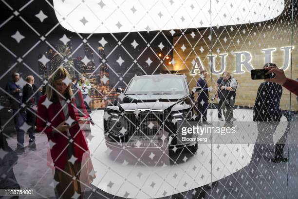 Attendees look at an Aurus Oo Senat sedan sits on display on the opening day of the 89th Geneva International Motor Show in Geneva Switzerland on...