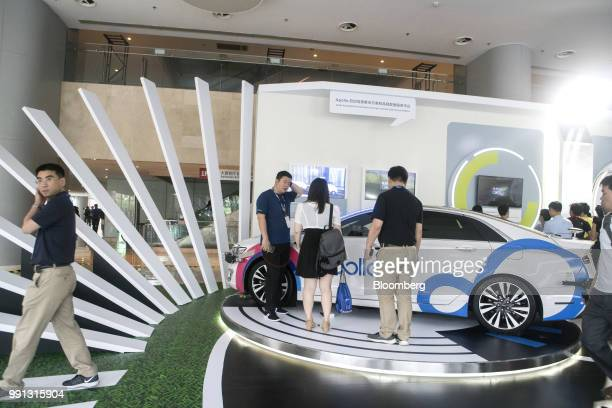 Attendees look at an autonomous vehicle that uses Baidu Inc Apollo technology on display during the Baidu Inc Create conference in Beijing China on...