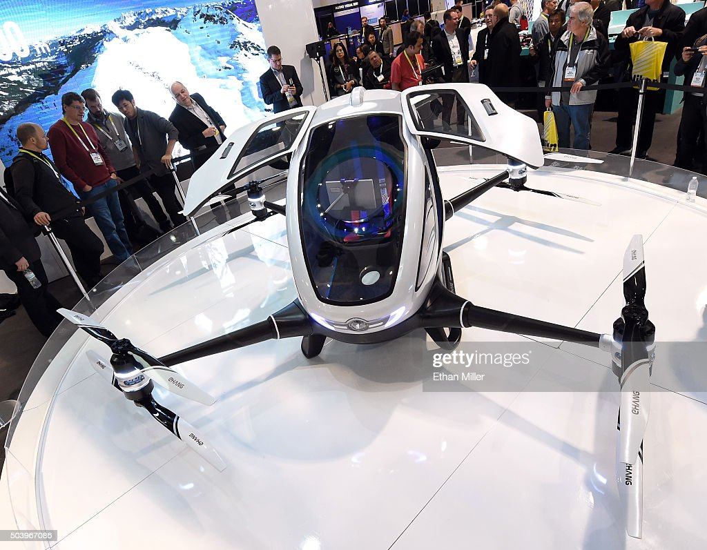 Attendees look at an EHang 184 autonomous-flight drone that can fly a person at CES 2016 at the Las Vegas Convention Center on January 7, 2016 in Las Vegas, Nevada. The 18-foot-long, 440-pound drone has four arms and eight propellers and can fly up to 63 mph for 23 minutes and go about 20 miles. It can carry one passenger who does not need to pilot the drone. Once a destination is entered, only a take off or land button needs to be pushed to travel. The drone takes off and lands vertically eliminating the need for a runway. CES, the world's largest annual consumer technology trade show, runs through January 9 and features 3,600 exhibitors showing off their latest products and services to more than 150,000 attendees.