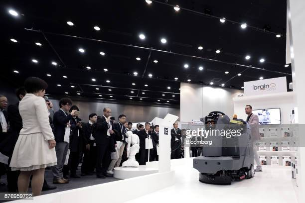 Attendees look at an International Cleaning Equipment RS26 rider auto scrubber powered by Brain Corp's Brain OS during a demonstration at the...