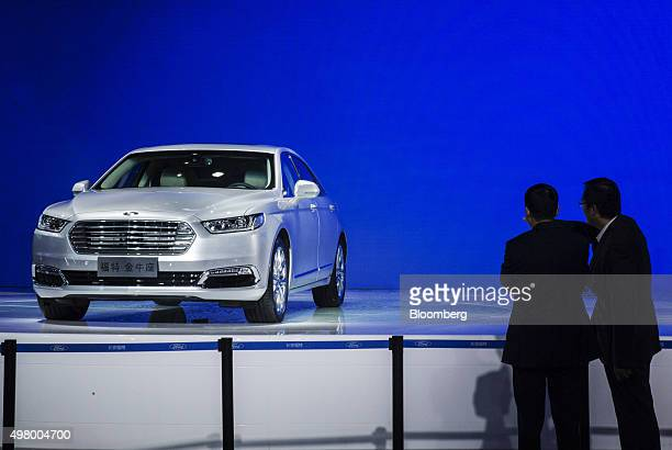 Attendees look at at a Ford Motor Co Taurus sedan on display during the China International Automobile Exhibition in Guangzhou China on Friday Nov 20...
