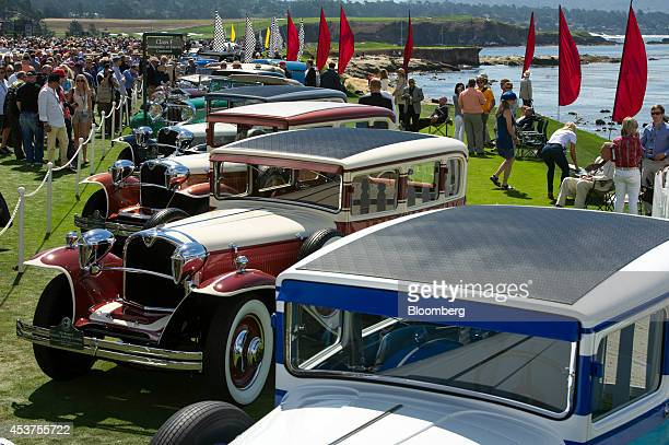 Attendees look at automobiles on display during the 2014 Pebble Beach Concours d'Elegance in Pebble Beach California US on Sunday Aug 17 2014 The...