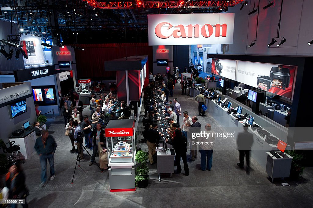 Attendees look at Canon Corp. products at the International Consumer Electronics Show (CES) in Las Vegas, Nevada, U.S., on Friday, Jan. 13, 2012. The 2012 CES trade show, which runs through Jan 13, features more than 2,700 global technology companies presenting consumer tech products and is expected to draw over 140,000 attendees. Photographer: David Paul Morris/Bloomberg via Getty Images