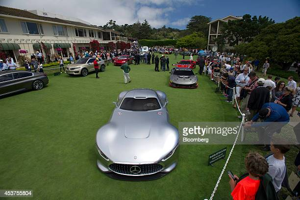 Attendees look at concept cars on display during the 2014 Pebble Beach Concours d'Elegance in Pebble Beach California US on Sunday Aug 17 2014 The...