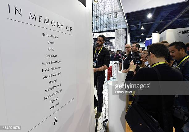 Attendees look at drones at the booth of the French company Parrot next to a sign placed in memory of the 12 victims of the terrorist attack in Paris...