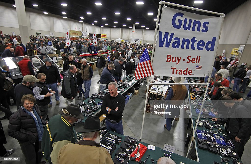 "Attendees look at guns at the Rocky Mountain Gun Show in Sandy, Utah, U.S. on Saturday, Jan. 7, 2012. The National Rifle Association called for stationing police officers in schools as the proper response to the Dec. 14, 2012 school shooting in Connecticut and blamed ""blood-soaked films"" and video games for the violence. Photographer: George Frey/Bloomberg via Getty Images"