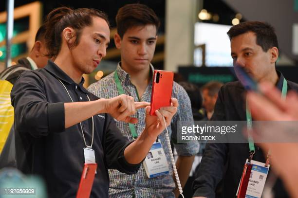 Attendees look at Huawei smartphones January 8 2020 at the 2020 Consumer Electronics Show in Las Vegas Nevada