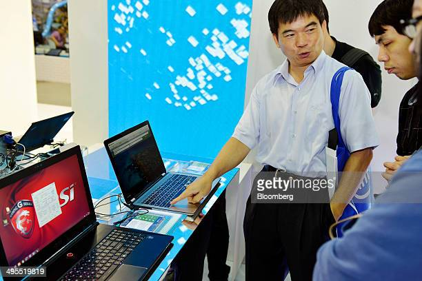 Attendees look at laptops at the Microsoft Corp booth during the Computex Taipei 2014 expo at the Taipei Nangang Exhibition Center in Taipei Taiwan...