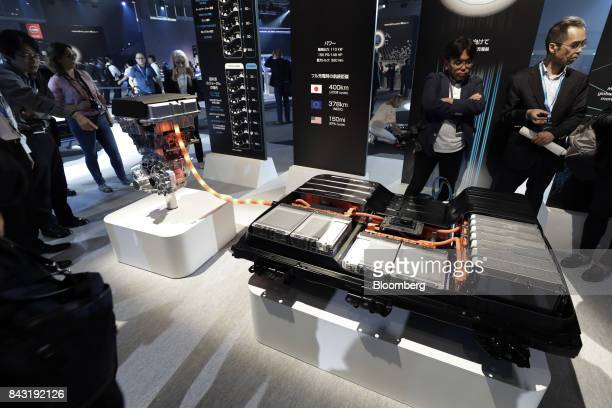 Attendees look at mockups of batteries right and a motor unit for Nissan Motor Co's new Leaf electric vehicle at the unveiling in Chiba Japan on...