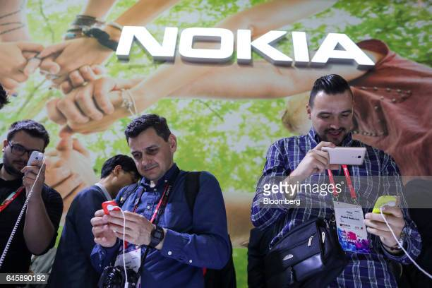 Attendees look at Nokia 3310 mobile phones manufactured by HMD Global Oy on the opening day of the Mobile World Congress in Barcelona Spain on Monday...
