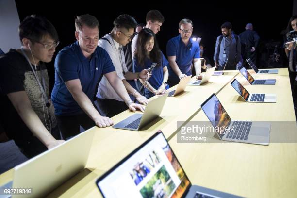 Attendees look at the new Apple Inc MacBook Pro laptop computers during the Apple Worldwide Developers Conference in San Jose California US on Monday...