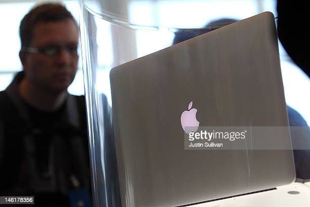 WWDC attendees look at the new MacBook Pro that is displayed following the keynote address at the Apple 2012 World Wide Developers Conference at...