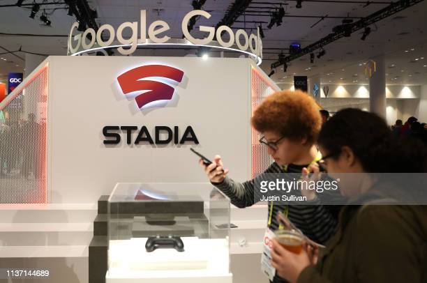 Attendees look at the new Stadia controller on display at the Google booth at the 2019 GDC Game Developers Conference on March 20 2019 in San...