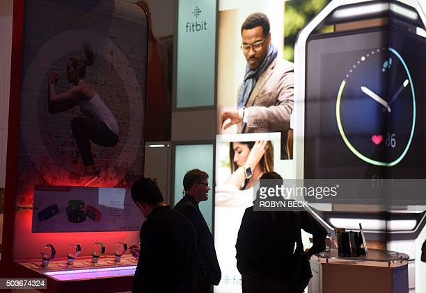 Attendees look at wearable's near the FitBit booth on the first day of the CES 2016 Consumer Electronics Show on January 6 2016 in Las Vegas Nevada...