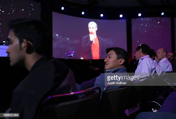 Attendees look on as Larry Page Google cofounder and CEO speaks during the opening keynote at the Google I/O developers conference at the Moscone...